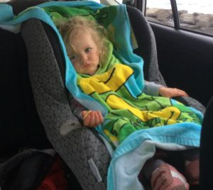 Girl in a car seat covered with a towel to try to decrease clean up in case of vomiting from motion sickness
