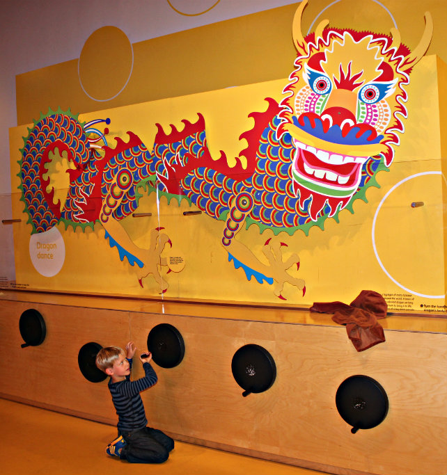 Child playing with a wall hung chinese dragon things for kids to do at the Musuem of Scotland