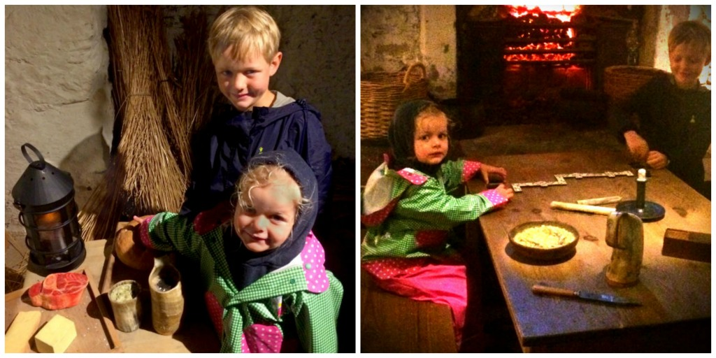 a boy and a girl pose for photos with fake food and a fake domino set, in the Prison of war exhibition at Edinburgh castle