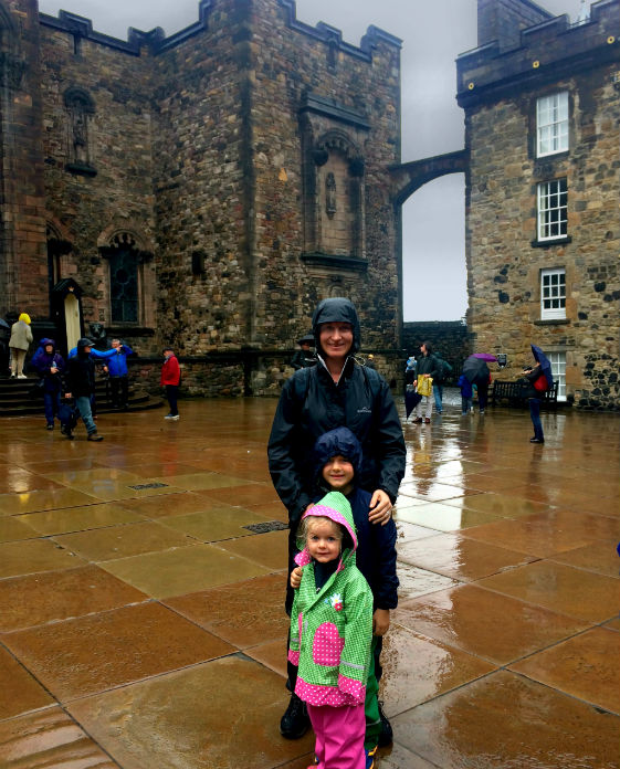 Standing on the roayal square, in the rain, edinburgh castle with children.