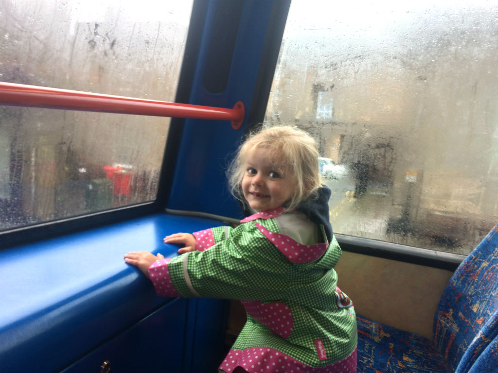 Young girl enjoying a ride on the top deck of a double decker bus in Edinburgh with kids.