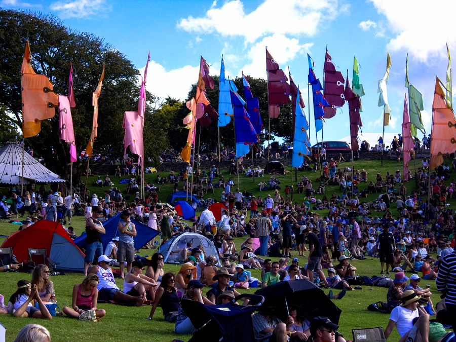 WOMAD is the best thing to do in New Plymouth if you are visiting the area in March. Festival goers sit in the grassy amphitheater and listen to music.