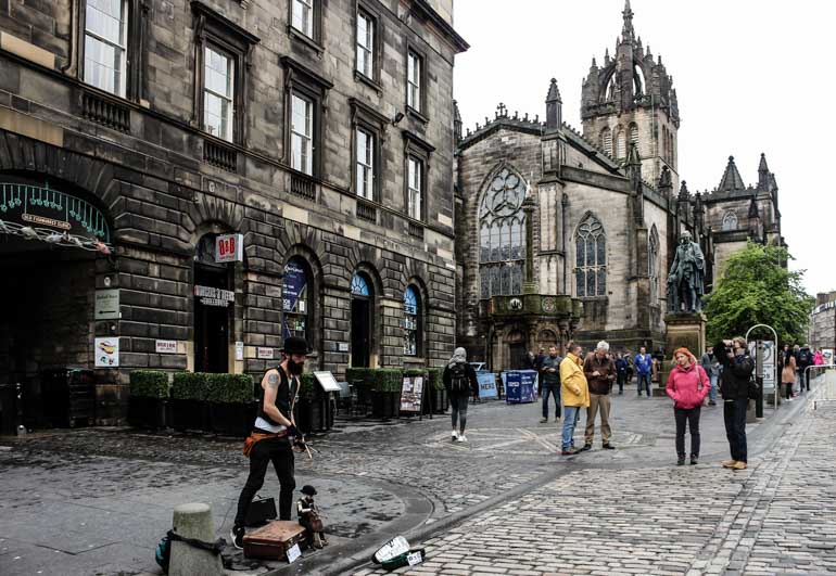 Start your Scotland road trip in Edinburgh. Man busking on the Royal Mile.