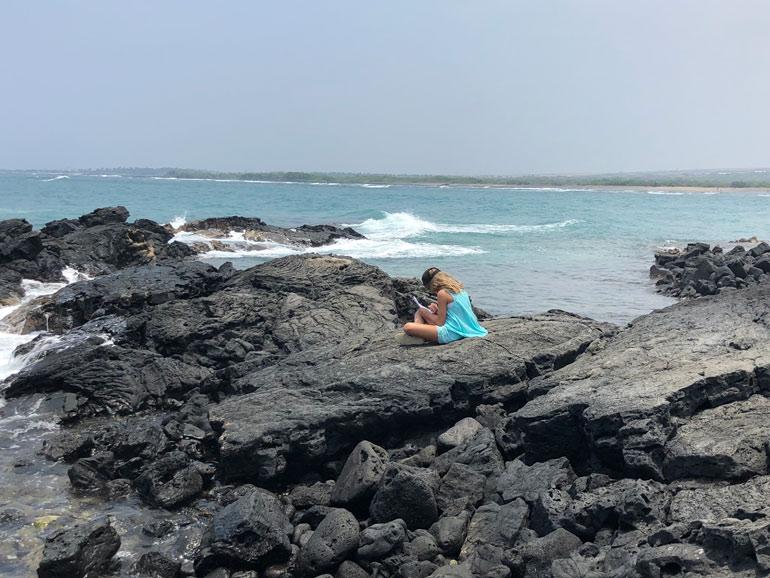 Girl sitting on the rocky foreshore at Kaloko-Honokohau National Historical Park in Hawaii