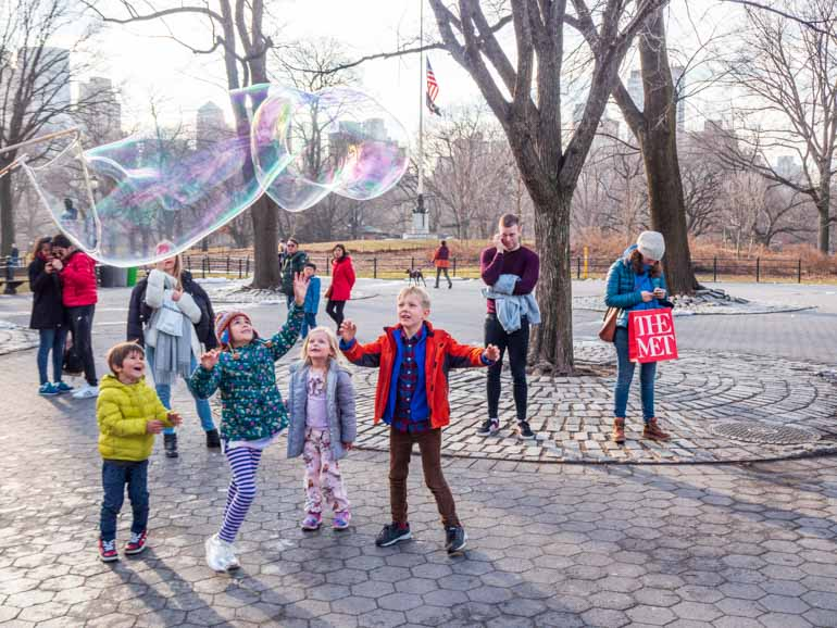 Kids visiting New York playing in central park with giant bubbles