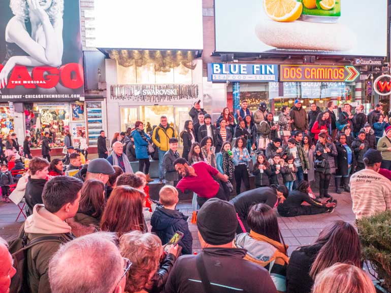 Kids watching street perfomance on New York City family holiday