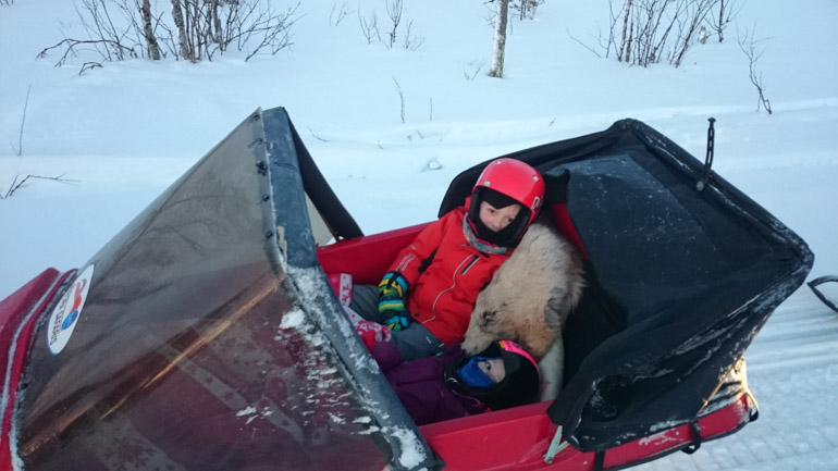 Baby and child in a sleigh in Lapland, Levi, Finland on a visit to Santa Claus