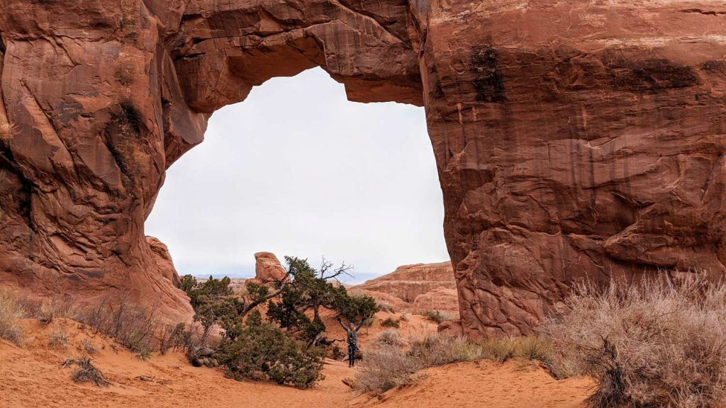 It is easy to stand under Pine tree arch in Arches National Park with kids