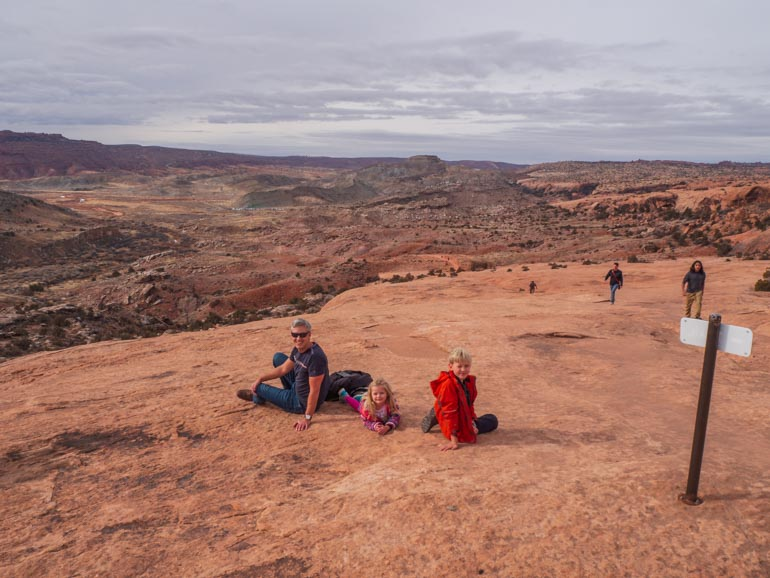 Taking a rest on the trail going up to Delicate Arch with kids in Arches National Park near Moab in Winter