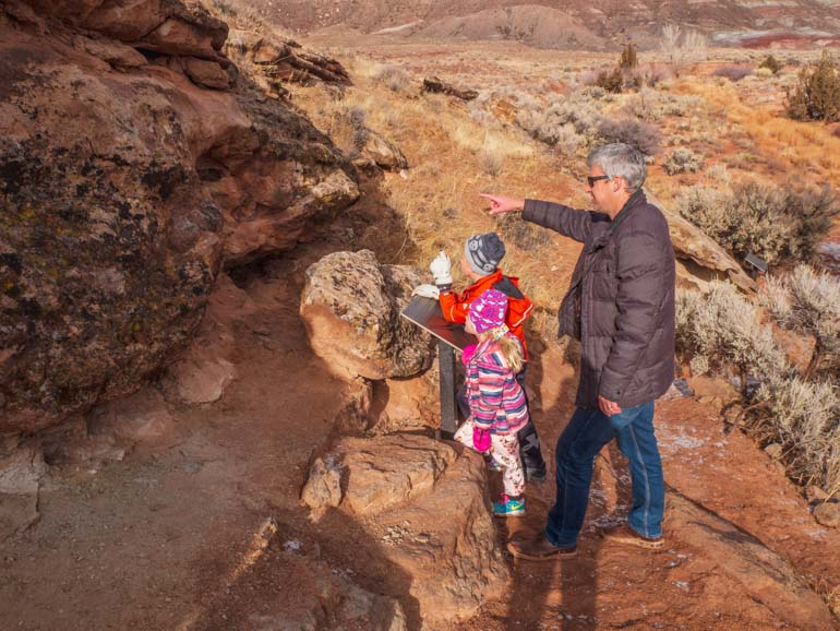 Family with kids spotting dinosaur bones on the trail near Moab, Utah